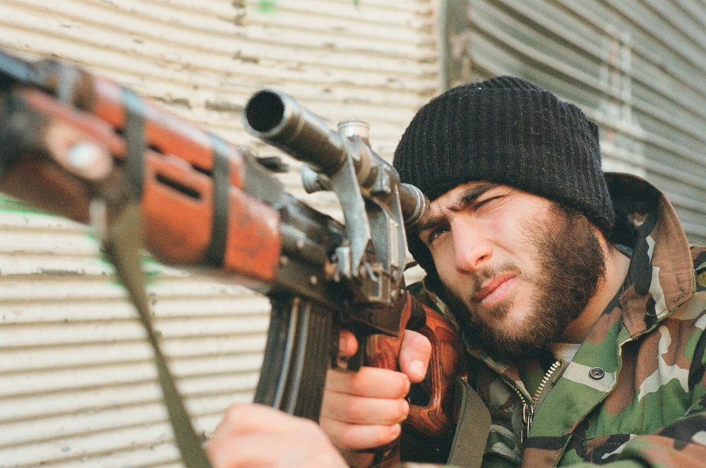 Nineteen-year-old Becker, an FSA fighter, aims his weapon towards enemy positions in Aleppo. F100 Portra 400
