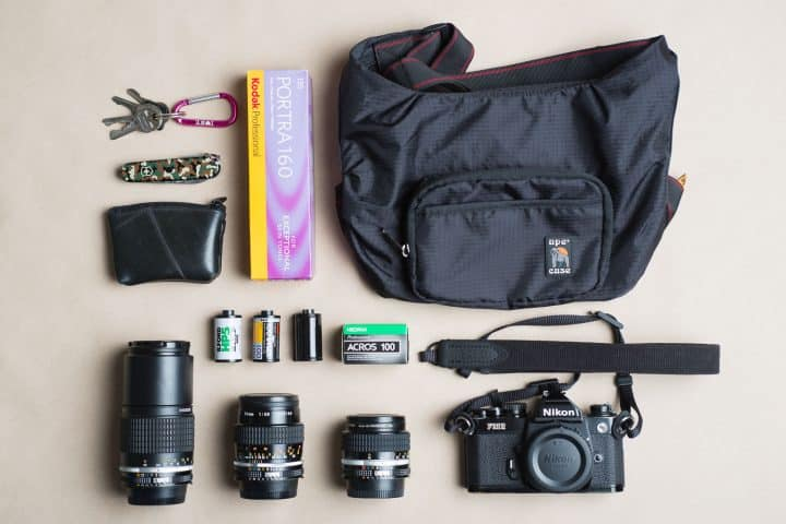 Nikon FE2 set with lenses inside a black camera bag with Kodak Portra 160 film